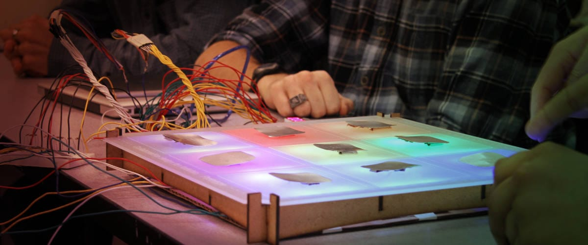 Photo of adults collaborating on Arduino light project